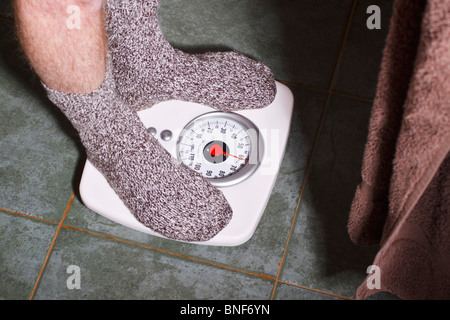 Man in socks weighing himself on a bathroom scale. - Stock Photo