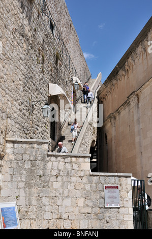Tourists using the steps rising from street level  at Pile Gate to the ramparts at the top of the Walls in Dubrovnik - Stock Photo