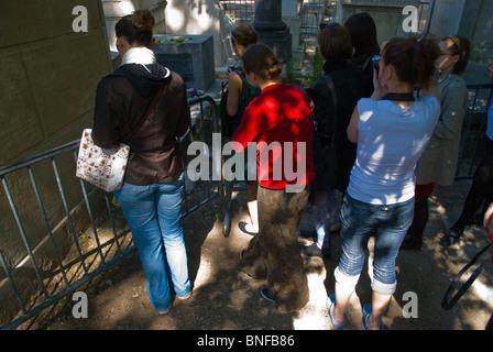 Young women at Jim Morrison's grave Cimetiere du Pere-Lachais 20th arrondissement Paris France Europe - Stock Photo