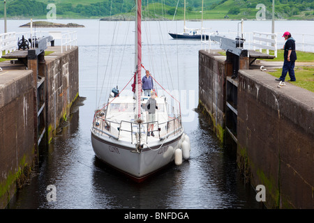 Yacht enters the first sea lock on the  Crinan canal - Stock Photo