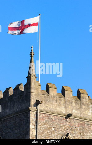 English Flag of St George flying from a church tower on a sunny day - Stock Photo