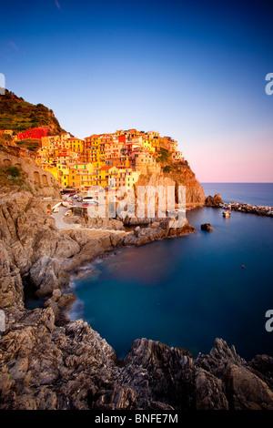 Last light of sunset on the hillside village of Manarola in The Cinque Terre, Liguria Italy - Stock Photo