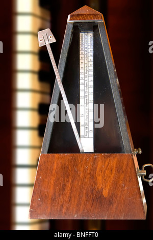 Old metronome over white table with vertical piano behind (vertical photo) - Stock Photo