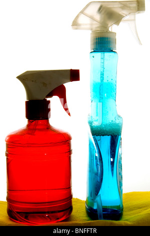 Two sprayers, one red and one blue, over yellow flannel - Stock Photo
