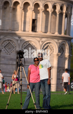 Tourist couple poses for camera in front of the Leaning Tower of Pisa, Tuscany Italy - Stock Photo