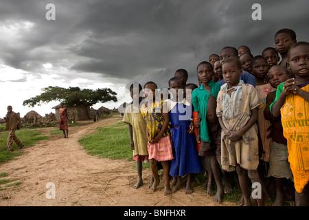 Group of poor children huddled together in a village in northern Uganda. - Stock Photo