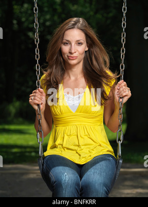 Young smiling attractive woman sitting on a swing in a park - Stock Photo