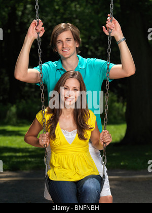 Young happy couple in their early thirties having fun on a swing at children's playground - Stock Photo