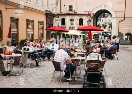 People sitting outside in a pavement cafe in the historic city. Hagenauer Platz, Salzburg, Austria, Europe. - Stock Photo