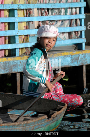 Little girl paddling on Tonle Sap Lake, Cambodia - Stock Photo