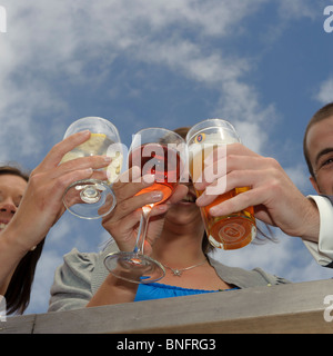 Three guests clinking their drinks glasses together at a wedding reception, UK - Stock Photo