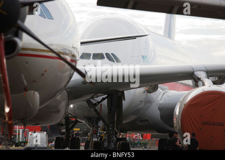 Security staff and static display aircraft lined-up at the Farnborough Airshow, the A380 at the back and a 777 in - Stock Photo