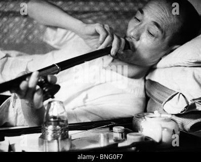 Mature man smoking opium - Stock Photo