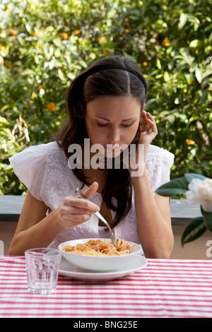 young caucasian woman eating spaghetti - Stock Photo