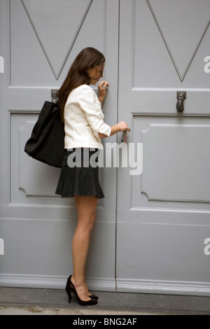 young woman opening a door - Stock Photo