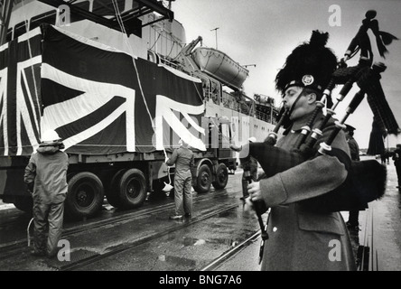 A military piper playing as a freightliner full of coffins returns from the Falklands War in 1982. - Stock Photo