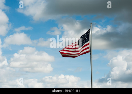 American flag on a flagpole blowing in the wind - Stock Photo
