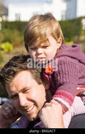 Vertical portrait of a young father carrying his cute daughter on his shoulders in the sunshine. - Stock Photo