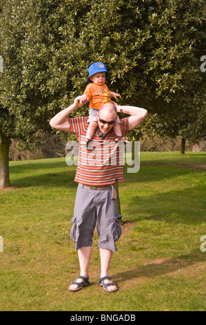 Vertical portrait of a young father carrying his young son on his shoulders in the sunshine. - Stock Photo
