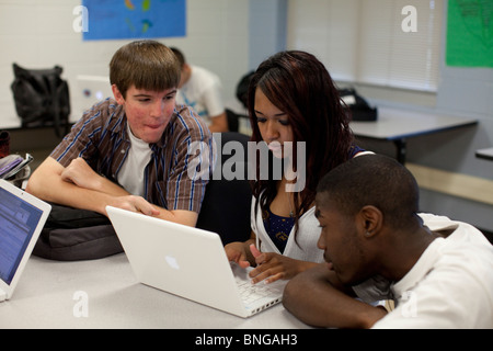 Ethnic, racial mix of students work together on project using laptop computer in classroom at Manor New Tech High - Stock Photo
