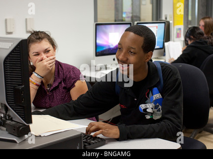 African-American boy and Anglo girl work together using computer on class project at Manor New Tech High School - Stock Photo