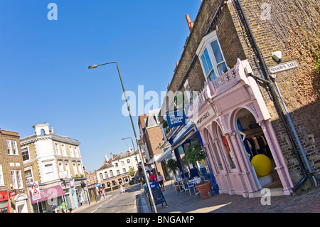 Horizontal wide angle of independent boutique shops on Wimbledon High Street in the sunshine. - Stock Photo