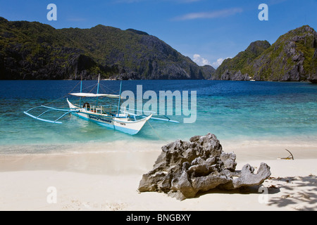 Our small boat anchored on a white sand beach on MATINLOC ISLAND near EL NIDO - PALAWAN ISLAND, PHILIPPINES - Stock Photo