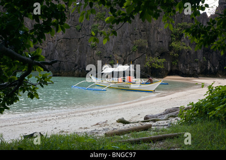 Our boat at a secluded beach on MATINLOC ISLAND near EL NIDO in the BACUIT ARCHIPELAGO - PALAWAN ISLAND, PHILIPPINES - Stock Photo