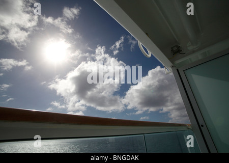 view from balcony of cruise ship looking at sky with sun shinning through clouds - Stock Photo