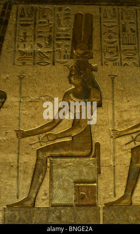 Ptolemaic temple of Hathor and Maat. Polychrome reliefs that decorate the interior. Hathor. Seated figure. Deir - Stock Photo
