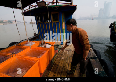 A fisherman on his boat in Xiamen, China - Stock Photo