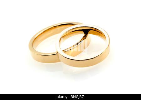 pair of golden wedding rings on white background - Stock Photo