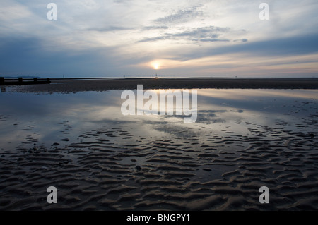 Evening skies and reflections at low tide.  On the horizon, the turbines of the Rhyl Flats wind farm can be seen. - Stock Photo