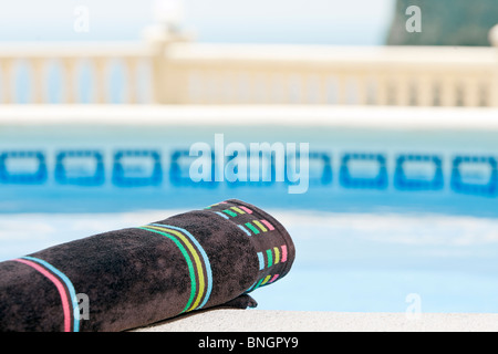 Shot of a Rolled Towel next to the Swimming Pool - Stock Photo