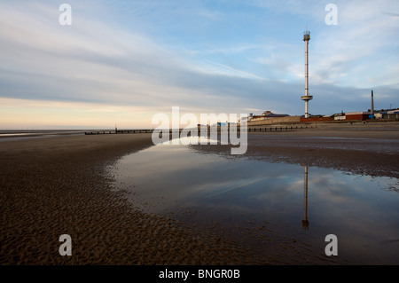 Rhyl sky tower is reflected in standing water on the beach at low tide towards sunset. - Stock Photo