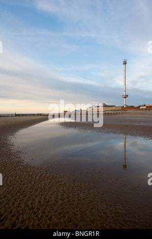 Rhyl sky tower is reflected in standing water on the beach at low tide nearing sunset. - Stock Photo
