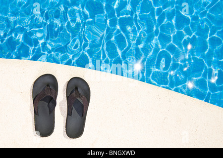 Shot of a Pair of Flip Flops next to the Pool - Stock Photo