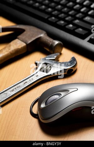 Metallic computer mouse, old tools placed next to compute keyboard - Stock Photo