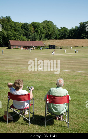 A couple watching a game of village cricket in the village of Lyminge near Folkestone, Kent, UK - Stock Photo