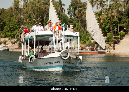 A ferryboat full of Western tourists on the river Nile at Aswan, Upper Egypt - Stock Photo