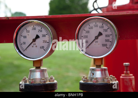 Two similar pressure gauges on heavy equipment - Stock Photo