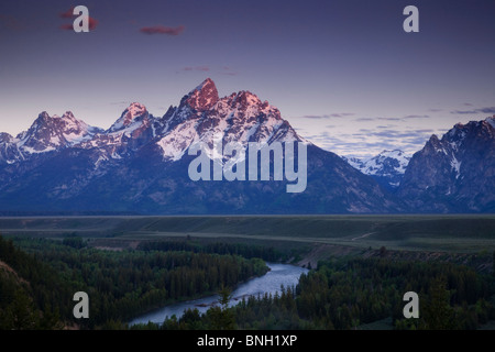 The mountains of Grand Teton National Park tower over a section of the Snake River, as seen from the Snake River - Stock Photo