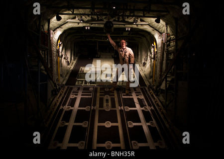 Loadmaster and raised ramp on a Lockheed Martin-built C-130J Super Hercules airlifter. - Stock Photo