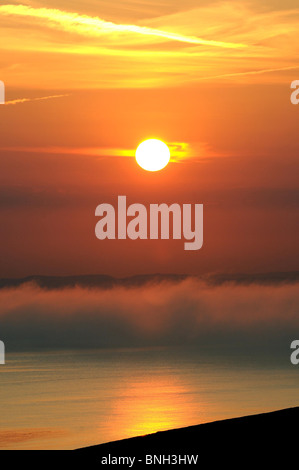 Heat wave and fog bank with sunsetting over Lyme Bay, viewed from Chesil beach. Dorset UK. - Stock Photo