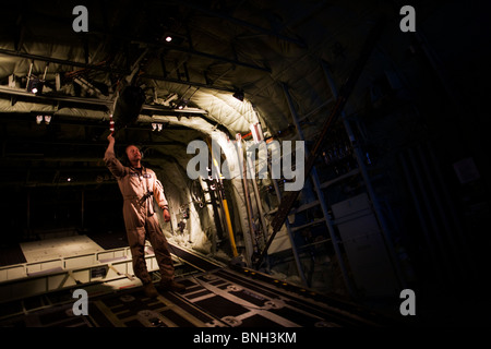 Loadmaster and raised ramp on a Lockheed Martin-built C-130J Hercules airlifter. - Stock Photo