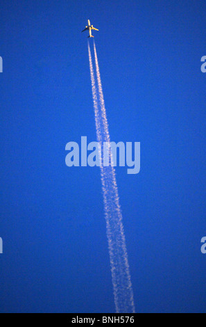 Aeroplane leaves contrails in the sky, jet plane leaving contrail - Stock Photo