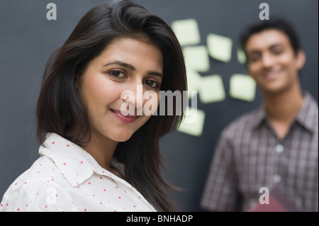 Portrait of a female college student smiling with her friend - Stock Photo