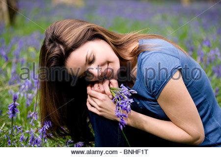 A young woman holding a bunch of bluebells - Stock Photo