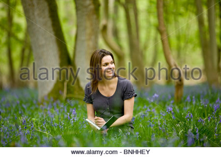 A young woman sitting amongst bluebells, drawing - Stock Photo
