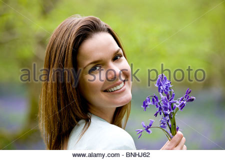 Portrait of a young woman holding a bunch of bluebells, close-up - Stock Photo